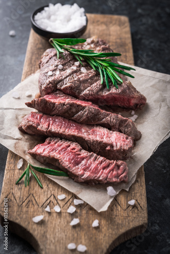 Fotografiet Grilled beef steak with rosemary and salt on cutting board