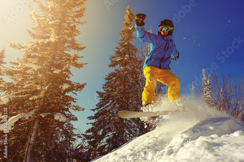 Snowboarder jumping through air with deep blue sky in background Canvas Print