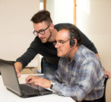 Fototapety Young man teaching eldery man of usage of computer. Intergenerat