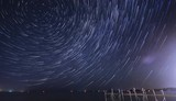 Stars rotating in a whirling mass of vortex moving over cottage pier on lake in summer