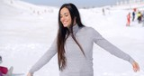 Young woman rejoicing in the winter weather standing in fresh snow at a ski resort with her arms open and head tilted back smiling at the sun.