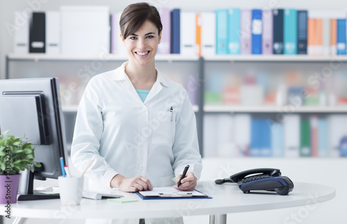 Smiling female doctor working at the clinic Plakat