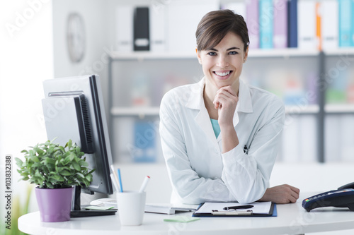 Attractive doctor posing at the clinic reception плакат