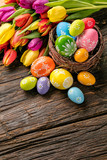 Fototapety Easter eggs and tulips on wooden planks