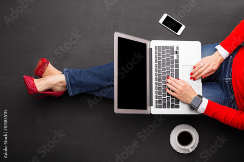 Woman sitting on ground at the office with computer in her lap