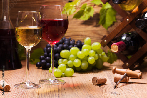 Glasses of red and white wine, served with grapes Poster