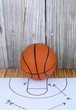An orange basketball and a play diagram good for March madness, championship or basketball season on wooden background