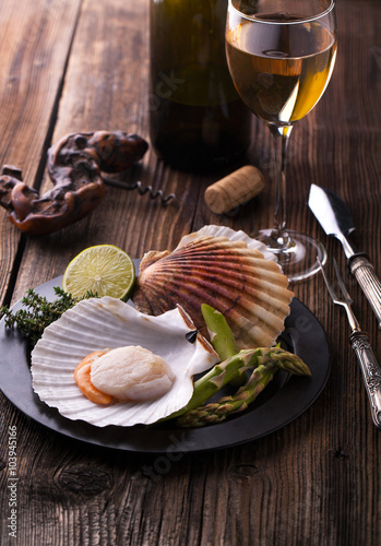 Poster Raw fresh scallops in the shell with lime, asparagus and a glass