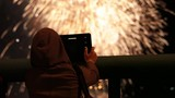 Girl using tablet to record firework pyrotechnic show