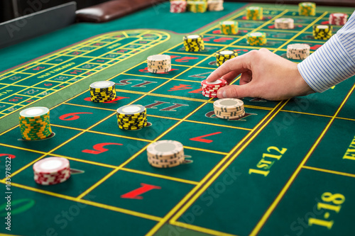 Picture of a green table and betting with chips. плакат