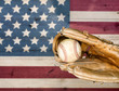 Weathered baseball mitt and ball with faded boards in USA flag colors