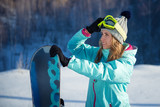 Portrait of beautiful cheerful woman with a snowboard
