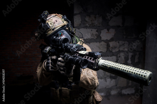 Plagát Special Forces soldier in protective uniform aimingg from rifle/ Special forces soldier wearing helmet and mask holding rifle with silencer aiming at camera