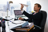 Fototapety Bored White Collar Worker Throwing Paper Airplane In Office
