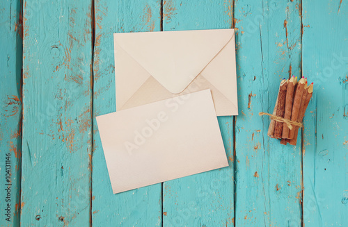 Poster top view image of blank letter paper and envelope next to colorful pencils on wooden table