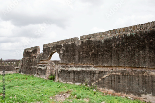 Depleting fort ruins with rocky green open space in front Poster