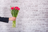 Fototapety Smiling businessman holding flowers  over white background. Bouq