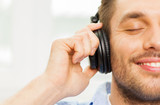 Fototapety smiling young man in headphones at home