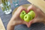 Fototapety frau zeigt ein herz mit den händen mit äpfeln im fokus