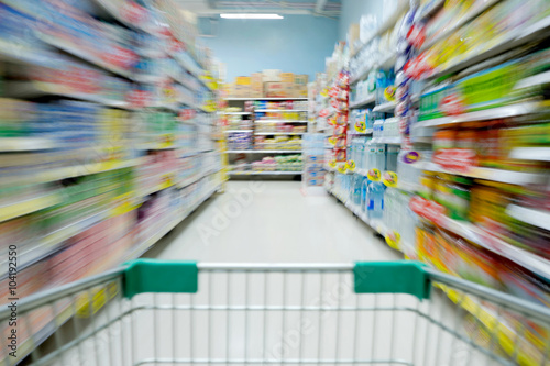 Shopping in supermarket shopping cart view with motion blur Poster