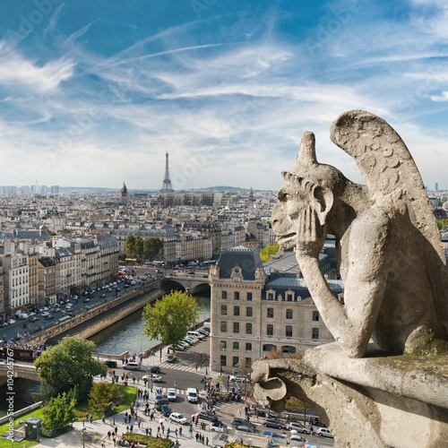 Gargoyle and city view from the roof of Notre Dame de Paris Photo by andriigorulko