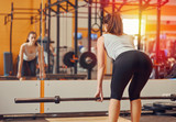 Fototapety Girl engaged in with a bar in the gym. Deadlift