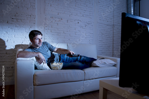 young attractive man at home lying on couch at living room watching tv holding r Poster