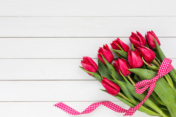 Red tulips bouquet decorated with ribbon. Copy space