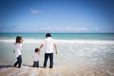 海でリラックスする四人家族