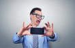 Funny businessman photographing himself on a smartphone. Concept antipathy