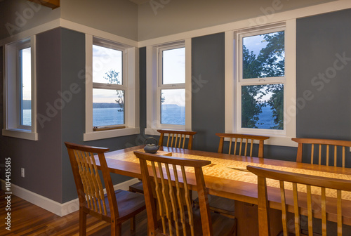 Dining area with wood table and chairs, painted walls and view windows with whit Poster