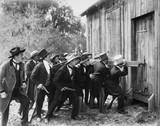 Group of men with guns and top hats breaking into a barn  - 104436742