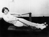 Woman using rowing machine  - 104441127