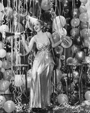 Woman celebrating with room full of balloons  - 104441165