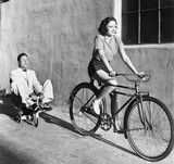 Woman on a bicycle pulling a grown man on a toy tricycle  - 104442179