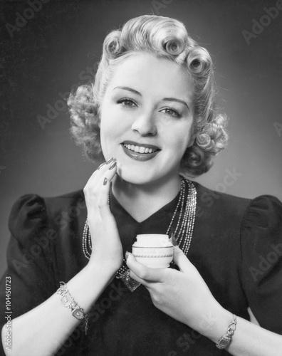 Portrait of woman applying makeup  - 104450723