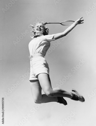 Woman jumping into the air with a tennis racket in her hand  - 104455738
