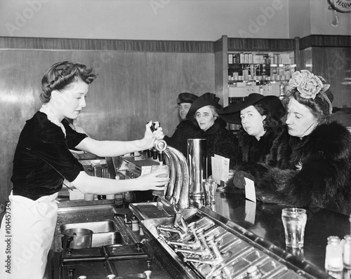 Three woman and a man sitting in a soda fountain  - 104457343