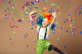 Fototapety Little boy in clown wig jumping and having fun celebrating birth