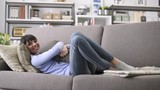Smiling young woman lying on the sofa at home, she is relaxing and hugging a soft pillow