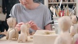 Tracking shot of young female artist making papier-mache dog figures of craft paper