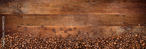 coffee background with beans on rustic old oak wood - 104485723