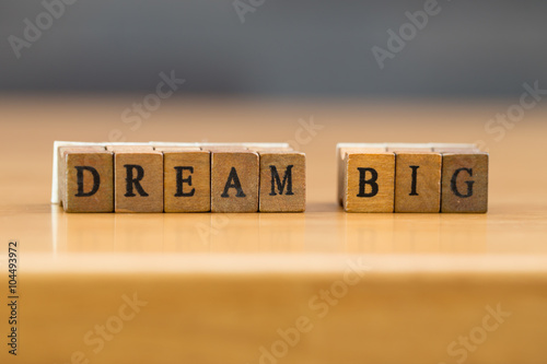 Dream big. word written on wood block плакат