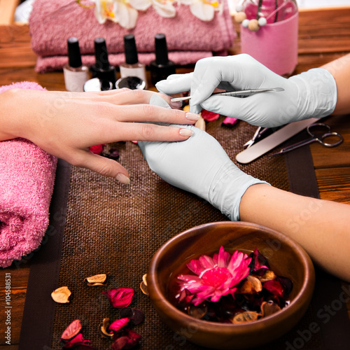 Closeup finger nail care by manicure specialist in beauty salon.  Poster