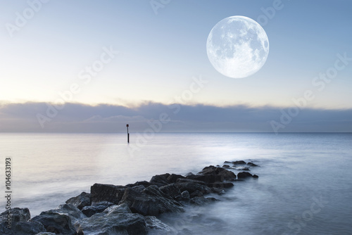 Stunning sunrise landscape over rocks in sea with super moon