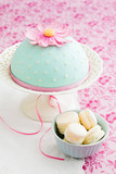 Round cake decorated with fondant and a sugar flower and macarons in a bowl