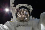 close up view of floating astronaut with a reflection of the space station showing (some elements courtesy of nasa)