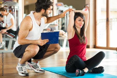 Koncepcja fitness, sport, trening, siłownia i styl życia - kobieta z osobistym trenerem