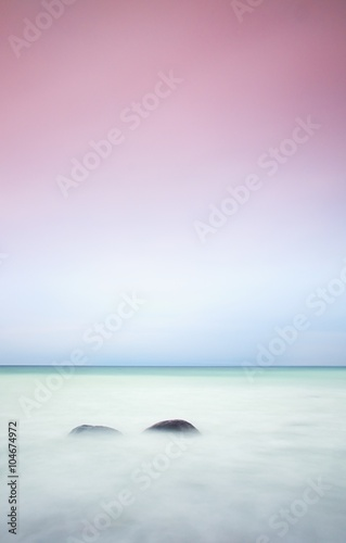 Romantic atmosphere in peaceful morning at sea. Big boulders sticking out from smooth wavy sea. Pink horizon - 104674972