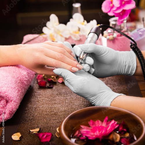 Plakát Closeup finger nail care by manicure specialist in beauty salon.